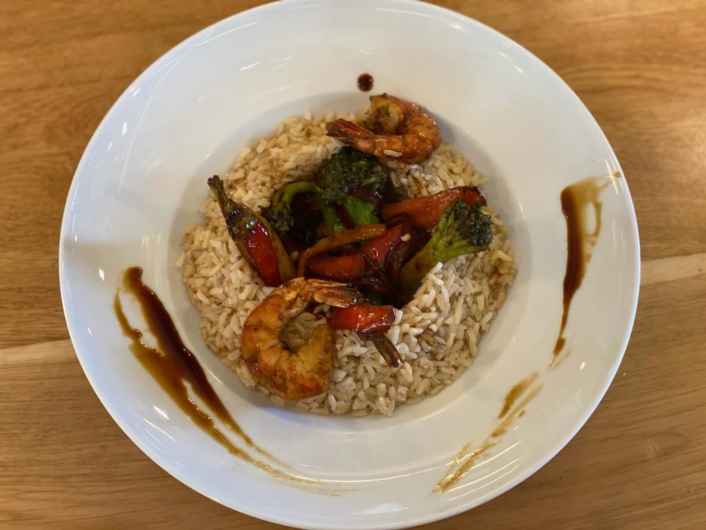 Creveți Black Tiger cu legume in stil asiatic pe pat de orez brun.